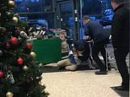 Security guard grapples with customer on the floor of supermarket entrance