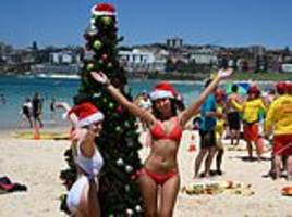 thousands dressed in festive beach outfits flock to bondi beach and byron bay to celebrate christmas