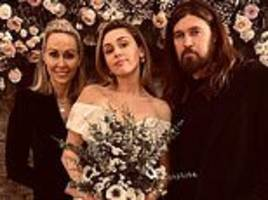 miley cyrus looks elegant in her first wedding portrait as she poses with her parents