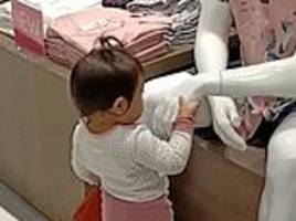 adorable moment toddler takes the hands of shop mannequins and gives them filipino greeting
