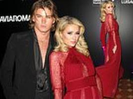 paris hilton looks ultra glam in a red semi-sheer gown as she cosies up to model jordan barrett