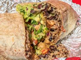 chipotle is considering raising prices as minimum wages rise, but the ceo says not to panic — they 'don't want to be like whole foods' (cmg)