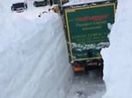 incredible footage shows truck clearing path for family stuck in a drift in austria