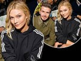 karlie kloss rubs shoulders with david beckham as they sit front row at adidas show