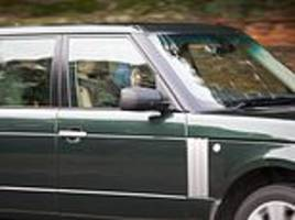 the queen is seen buckled-up driving range rover out of sandringham estate
