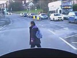 Heart-stopping moment schoolgirl is almost hit by a double decker bus as she crosses the road