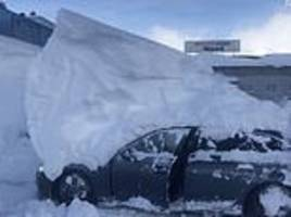driver tries to reverse audi out of a parking space but takes a six-foot pile of snow with him