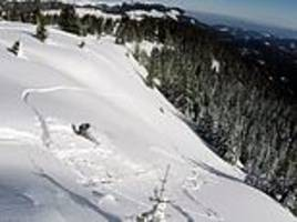 snowboarder falls after a jump and triggers an avalanche which carries him down the mountainside