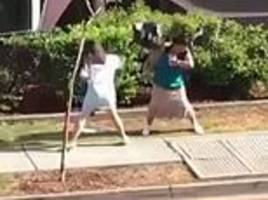 two middle-aged women trade blows with an umbrella and handbag outside an rsl club