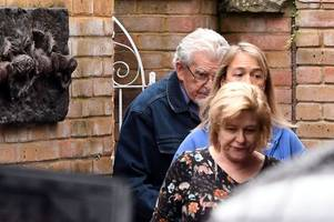 Rolf Harris pictured emerging from home after entering school grounds to wave at kids