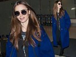 lily collins looks chic in bright blue coat and quirky shades as she touches down in los angeles