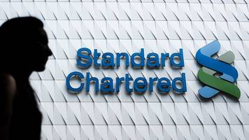 standard chartered puts aside $900m for potential fines