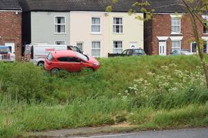 residents look on in disbelief as car gets trapped in ditch and dangles perilously over drain