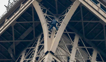 eiffel tower evacuated after man scales french landmark