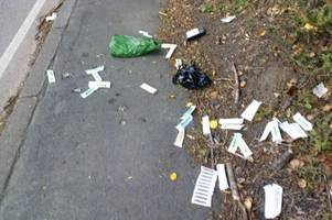 pile of discarded needles and syringes dumped on pavement next to busy road