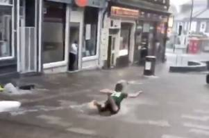 watch stirling street turn into 'water park' as youngsters dive through floods