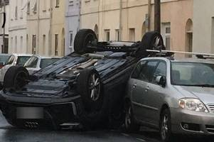 driver arrested after car flips onto its roof and gets wedged in parking spot