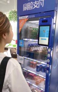 a futuristic chinese tiktok video shows a woman paying for vending machine items with no money or card — just her face