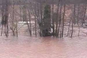 video footage shows shipping containers flowing down river near gloucestershire border