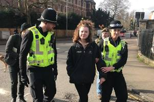 cambridge extinction rebellion protesters clap and cheer as member is led away by police
